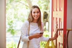 Mujer joven que vuelve a casa para el trabajo con compras imágenes de archivo libres de regalías