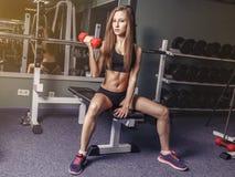 Mujer joven real de la aptitud para levantar pesa de gimnasia de los pesos su bíceps Fotos de archivo libres de regalías