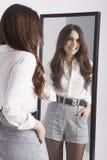Mujer joven real que mira en un espejo Imagen de archivo libre de regalías