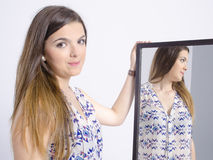 Mujer joven real que mira en un espejo Foto de archivo libre de regalías