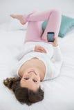 Mujer joven relajada con el teléfono móvil en cama Foto de archivo libre de regalías