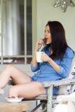 Mujer joven relajada con una taza de café y de galletas de la consumición Fotografía de archivo