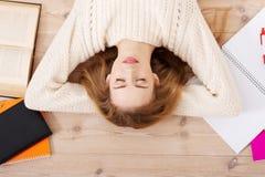Mujer joven relajada del estudiante que miente en el piso Fotos de archivo