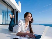 Mujer joven relajada en casa que trabaja en el ordenador portátil Imagen de archivo libre de regalías
