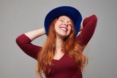 Mujer joven relajada en el sombrero vinoso que presenta con el beh de las manos Fotografía de archivo