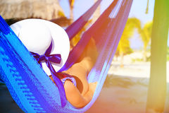 Mujer joven relajada en hamaca en la playa Imagenes de archivo