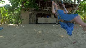 Mujer joven relajada en oscilaciones azules del vestido en el oscilaci?n de la cuerda en la playa arenosa reservada el d?a solead almacen de metraje de vídeo