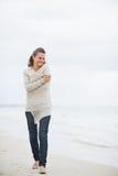 Mujer joven relajada en suéter que camina en la playa sola Imágenes de archivo libres de regalías