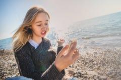Mujer joven relajada feliz que medita en una actitud de la yoga en la playa imagenes de archivo