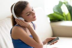 Mujer joven relajada que disfruta de música en auriculares usando el ap móvil Fotos de archivo