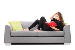 Mujer joven relajada que lee un libro asentado en el sofá Imagenes de archivo