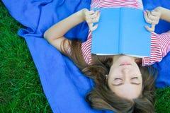 Mujer joven relajada que lee un libro que miente en una manta en la ley Imagen de archivo libre de regalías