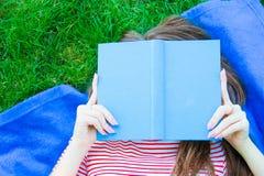 Mujer joven relajada que lee un libro que miente en una manta en la ley Foto de archivo