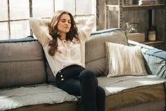 Mujer joven relajada que se sienta en el apartamento del desván Imagen de archivo libre de regalías