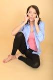 Mujer joven relajada que se sienta en el piso que tira de expresiones faciales Fotografía de archivo libre de regalías
