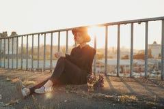 Mujer joven relajada que se sienta en el puente Fotos de archivo libres de regalías