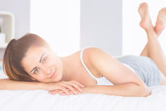 Mujer joven relajada sonriente que miente en cama Foto de archivo libre de regalías