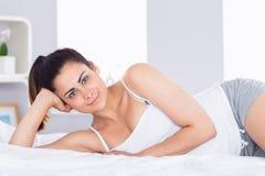 Mujer joven relajada sonriente que miente en cama Imágenes de archivo libres de regalías