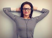 Mujer joven relajante feliz en auriculares que escucha el musi tranquilo Foto de archivo libre de regalías