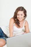 Mujer joven Relaxed en cama con la computadora portátil Fotos de archivo libres de regalías