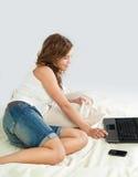 Mujer joven Relaxed en cama con la computadora portátil Fotos de archivo