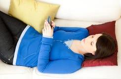 Mujer joven Relaxed que envía un mensaje en el sofá Imagen de archivo libre de regalías