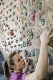 Mujer joven resuelta que sube para arriba una pared que sube en un gimnasio que sube interior Imagen de archivo libre de regalías