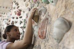 Mujer joven resuelta que sube para arriba una pared que sube en un gimnasio que sube interior Foto de archivo