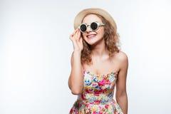 Mujer joven rizada alegre hermosa en gafas de sol y sombrero de paja, sobre un fondo blanco imagenes de archivo