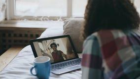 Mujer joven rizada que tiene charla video en línea con el amigo que usa la cámara del ordenador portátil mientras que miente en c Fotografía de archivo