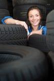 Mujer joven rodeada por los neumáticos del coche Imagen de archivo libre de regalías