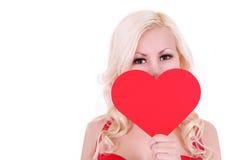 Mujer joven rubia con el corazón de la tarjeta del día de San Valentín, aislado Imagen de archivo libre de regalías