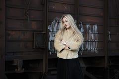 Mujer joven rubia contra un tren de carros Imagen de archivo libre de regalías