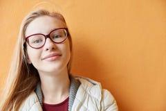 Mujer joven rubia delante de una pared Imágenes de archivo libres de regalías