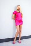 Mujer joven rubia en el vestido rosado que presenta cerca del edificio moderno Fotografía de archivo