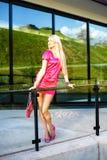 Mujer joven rubia en el vestido rosado que presenta cerca del edificio moderno Fotos de archivo libres de regalías