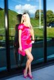 Mujer joven rubia en el vestido rosado que presenta cerca del edificio moderno Imágenes de archivo libres de regalías