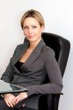 Mujer joven rubia en silla negra de la oficina Foto de archivo libre de regalías