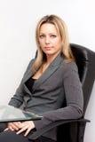 Mujer joven rubia en silla negra de la oficina imagen de archivo libre de regalías