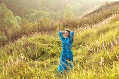 Mujer joven rubia en vestido contra la madera fotos de archivo