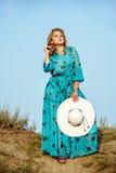 Mujer joven rubia en vestido y sombrero contra el cielo fotografía de archivo