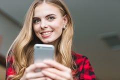 Mujer joven rubia encantadora alegre que usa smartphone Imagenes de archivo