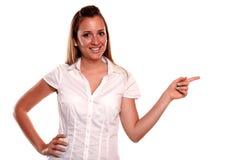 Mujer joven rubia encantadora que señala a su izquierda Fotos de archivo