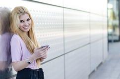 Mujer joven rubia feliz al aire libre usando su teléfono móvil aislado Foto de archivo libre de regalías