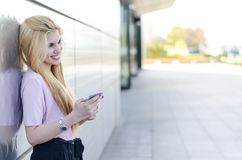 Mujer joven rubia feliz al aire libre usando su teléfono móvil aislado Foto de archivo