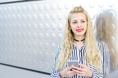 Mujer joven rubia feliz al aire libre usando su teléfono móvil aislado Imagenes de archivo