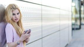 Mujer joven rubia feliz al aire libre usando su teléfono móvil aislado Fotografía de archivo libre de regalías