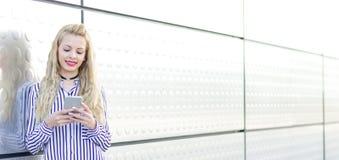 Mujer joven rubia feliz al aire libre usando su teléfono móvil aislado Fotos de archivo libres de regalías