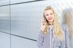 Mujer joven rubia feliz al aire libre usando su teléfono móvil aislado Imagen de archivo