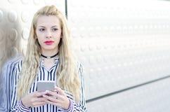 Mujer joven rubia feliz al aire libre usando su teléfono móvil aislado Fotografía de archivo